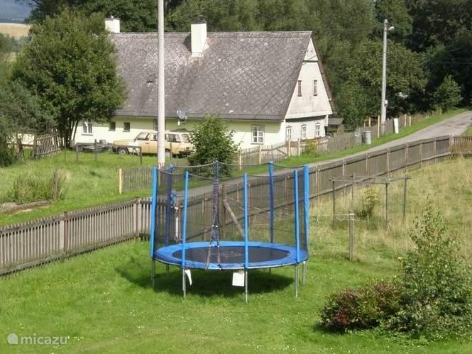Tuin met trampoline en aan de overkant het huis van de verhuurder.