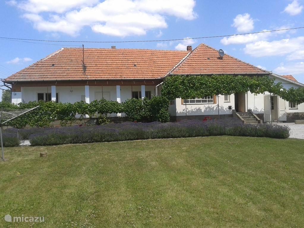 Zijkant van het huis, met een lekker grasveldje om te voetballen of cricketten