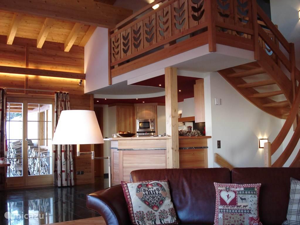 Vanuit de zithoek, zicht op de keuken en door het raam op de houtvoorraad.