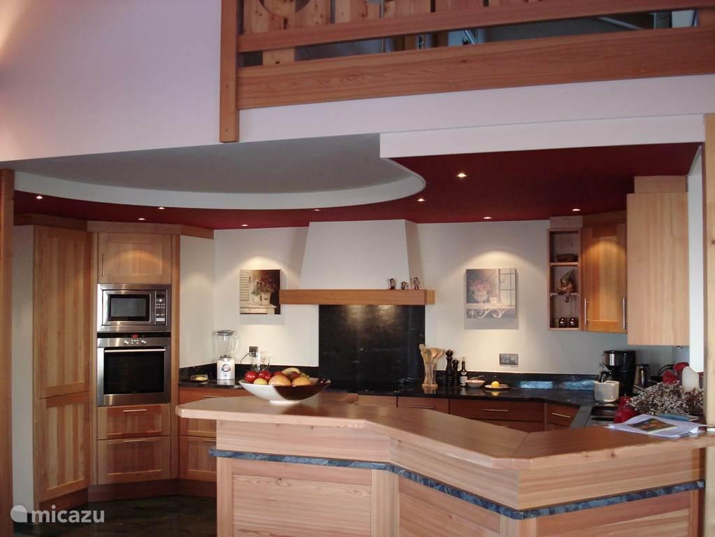 De open keuken is van alle gemakken voorzien. De bar is een plekje om even lekker te zitten.