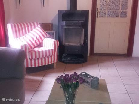 Gezellige woonkamer met televisie met nederlandse zenders , houtkachel voor de frisse avonden, 2 twee zitsbanken en fijne stoel. Het plafond is nog in orginele staat.