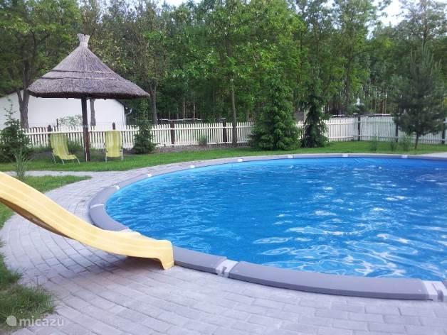 Prachtig mooi zwembad wat gedeeld word van 8 mtr doorsnede en 1,20 mtr diep  met kinderglijbaan,  tuindouche en rieten parasol met ligstoelen