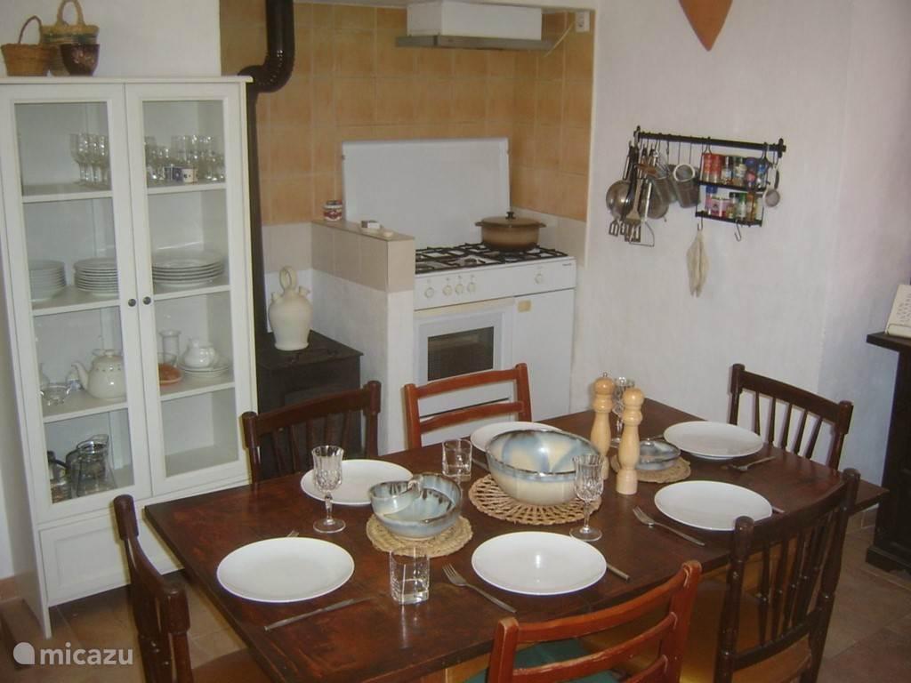 keuken met op de achtergrond het fornuis en de houtkachel