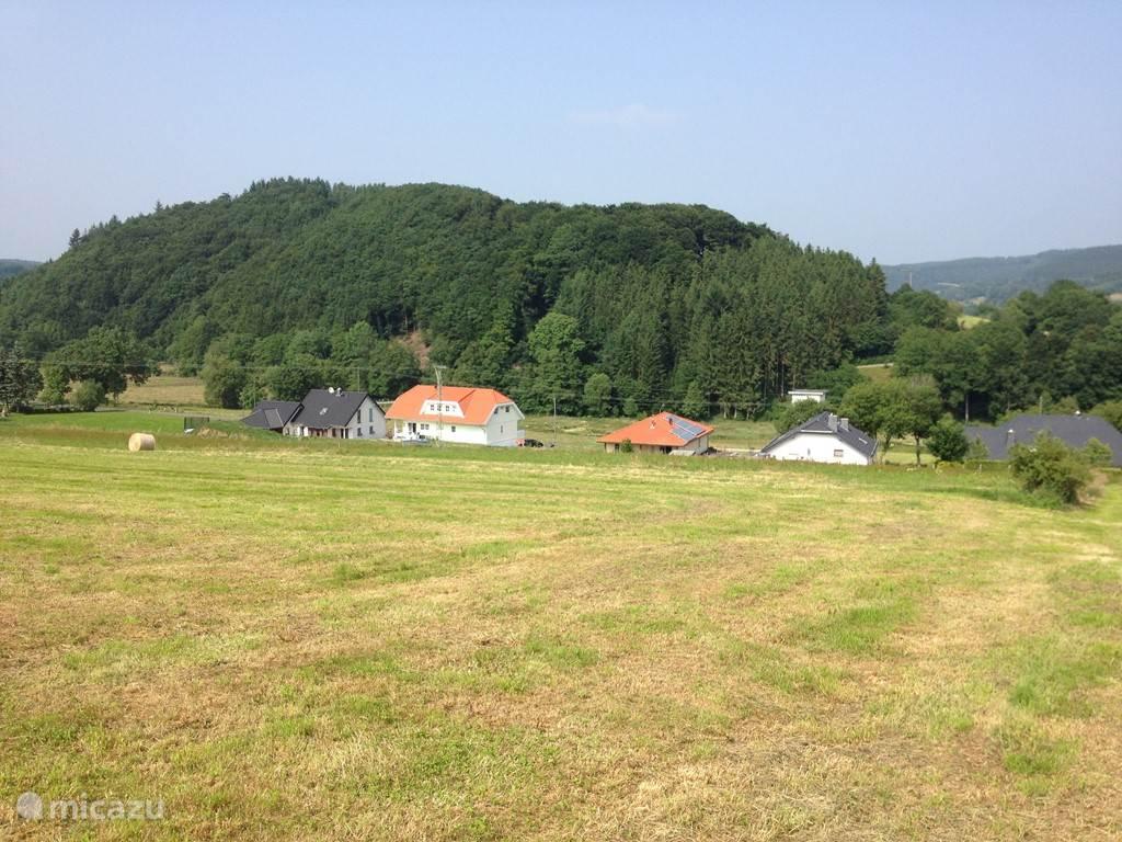 Aanzicht van het appartementengebouw en de bungalow vanaf de heuvel.