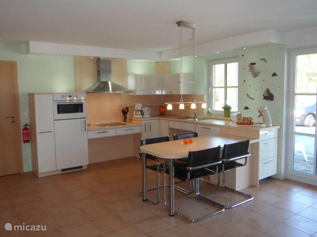Keuken vanuit de woonkamer met ruimte onder de spoelbak en kookplaat voor een rolstoel.