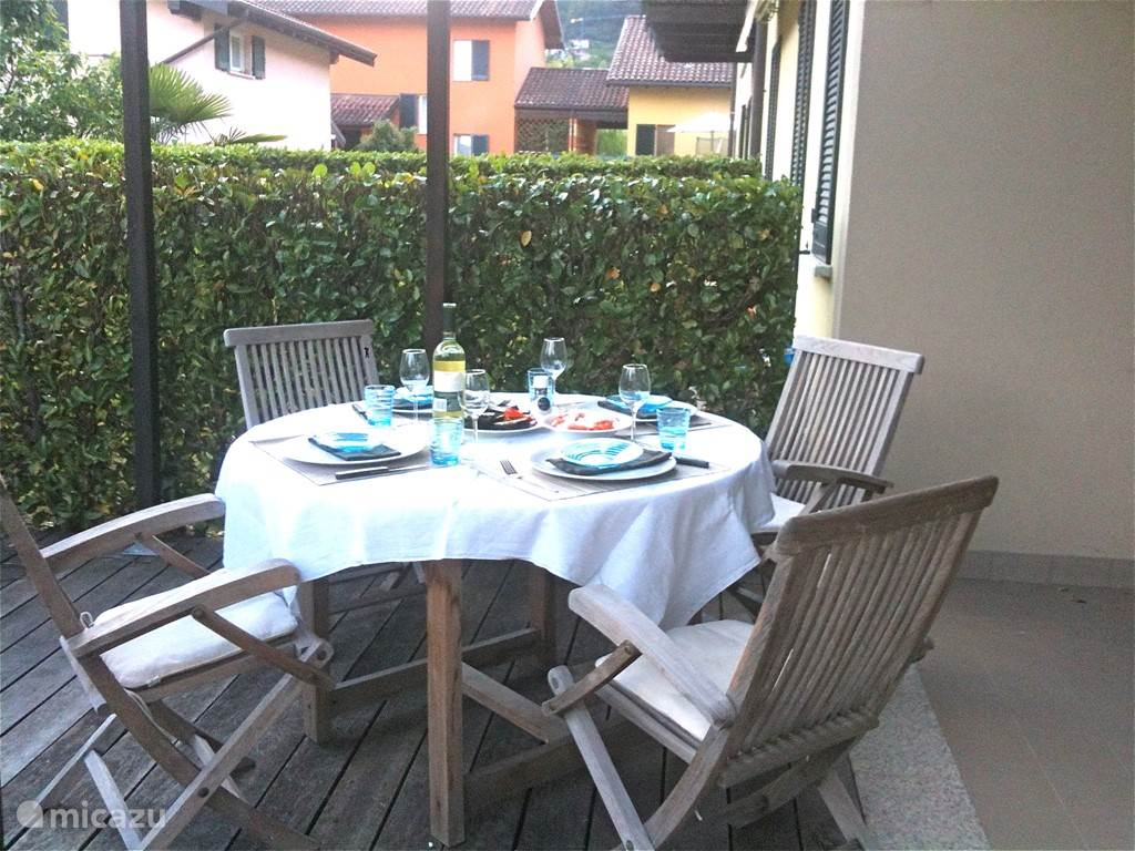 Terrace with a round table and four chairs in teak wood pieces on the south side of the apartment. There are two pieces electric sun screens present.