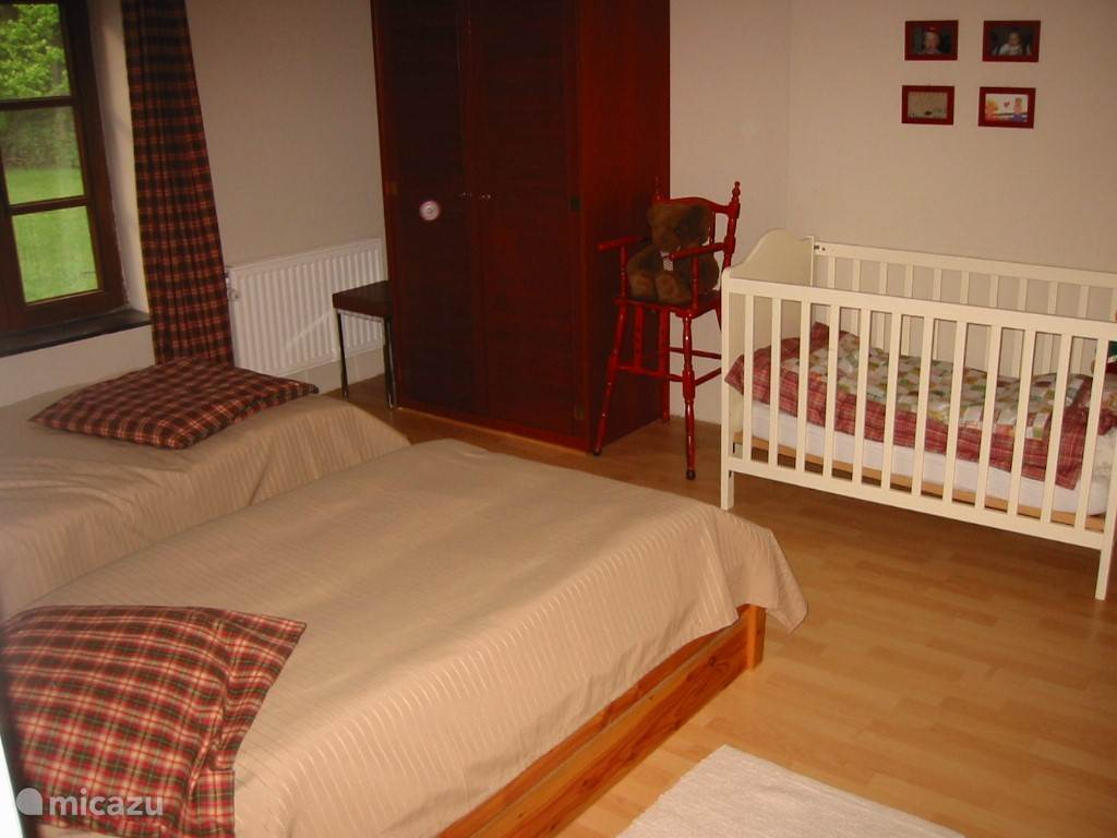 Front bedroom with two single beds and a cot