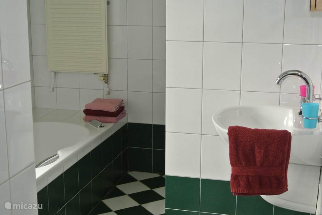 Badkamer met ligbad met bubbels en douche er naast