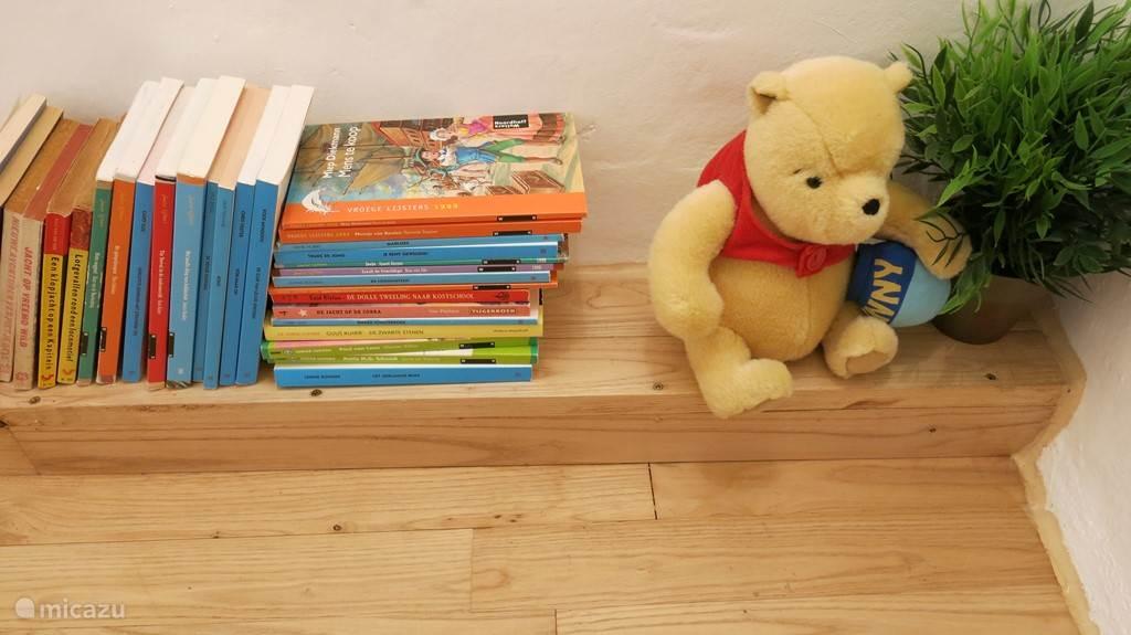 Kinderboeken  in een hoekje op de overloop. Spelletjes en speelgoed zijn in de leefkeuken.