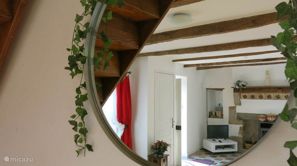 Detail huiskamer met via de spiegel een deelblik op de schouw en houtkachel.
