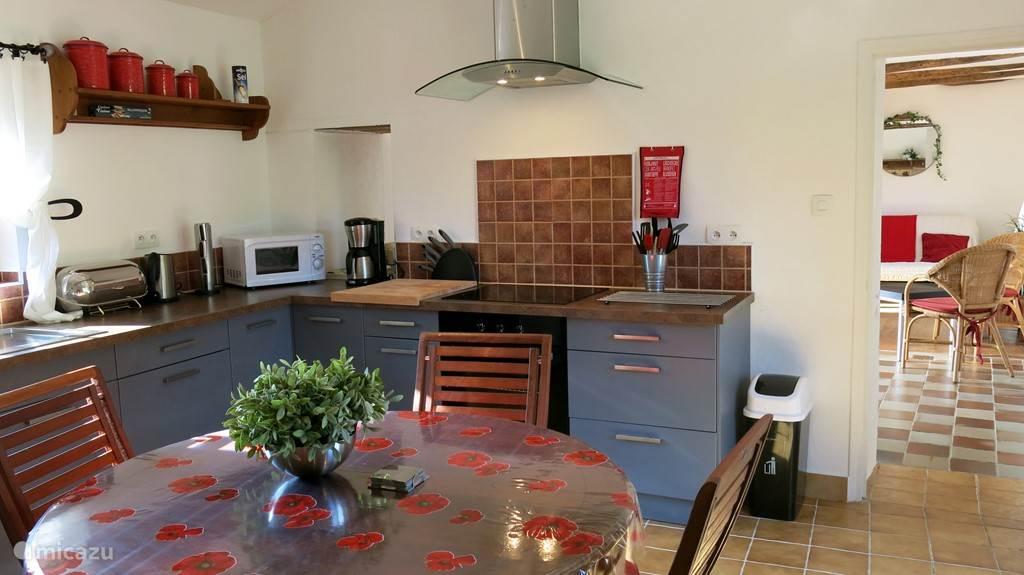 Compleet ingerichte zonnige en lichte woonkeuken met doorgang naar huiskamer (rechts op de foto).