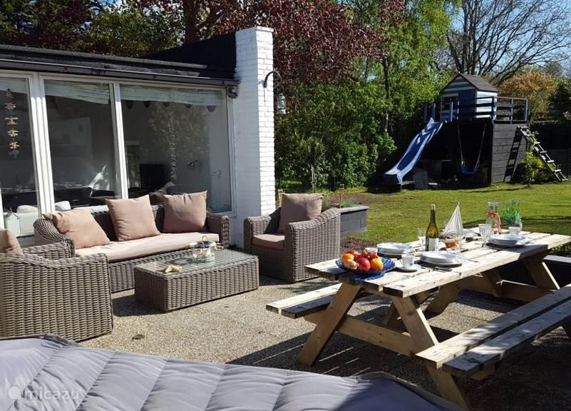 Veel ruimte met eejn heerlijke loungeset met uitzicht op boomhut met glijbaan en schommel.