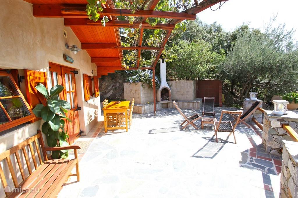 Het grote zonnige terras met douche en open vuurplaats.
