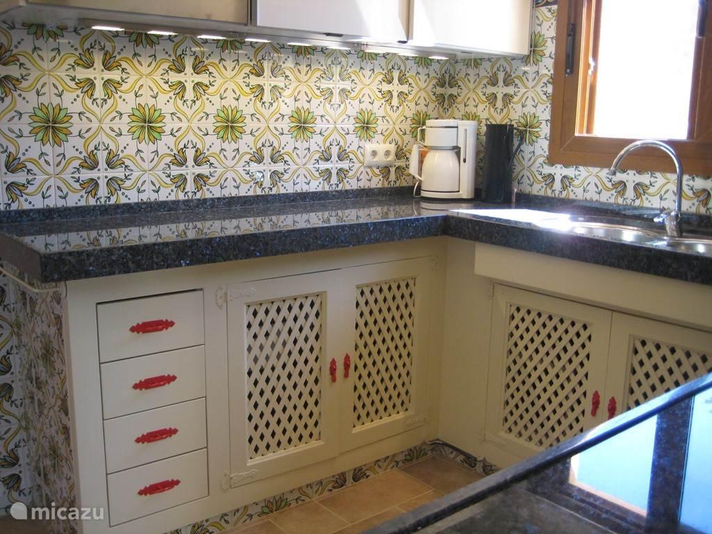 Keuken met handmade tegels, is toegerust met inductiekookplaat, magnetron/oven, vaatwasmachine en koel/vrieskast