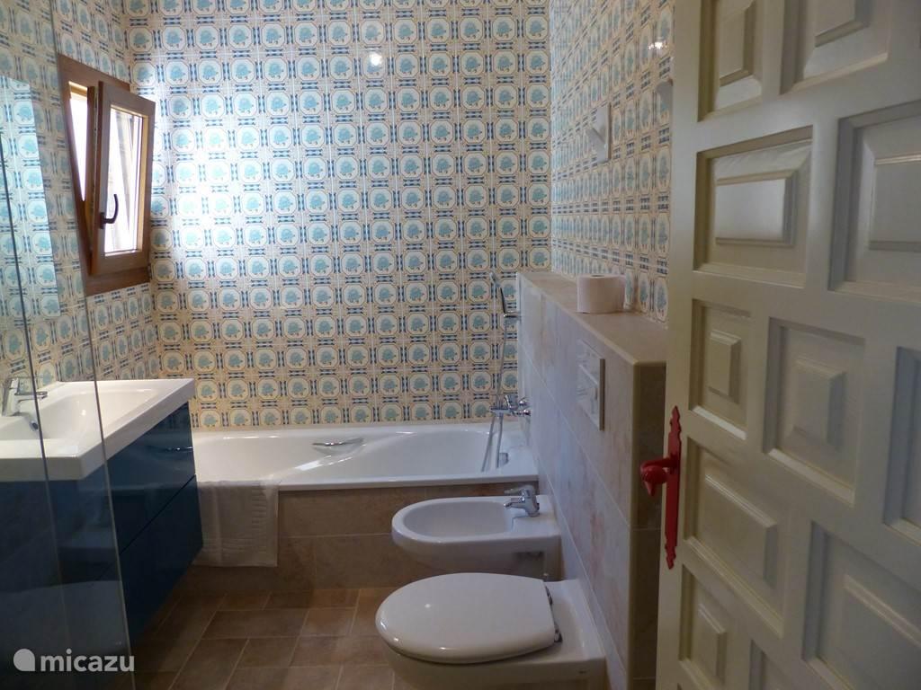 Badkamer 1, met de traditionele tegels. Vrijdragend bidet en wc,inloop douche en vloerverwarming.