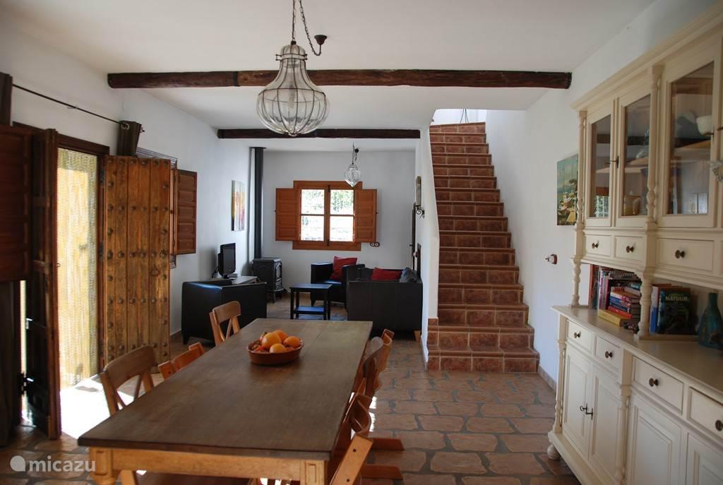 Eethoek met grote eettafel voor 10 personen, comfortabele zithoek en trap naar de eerste verdieping met slaapkamers