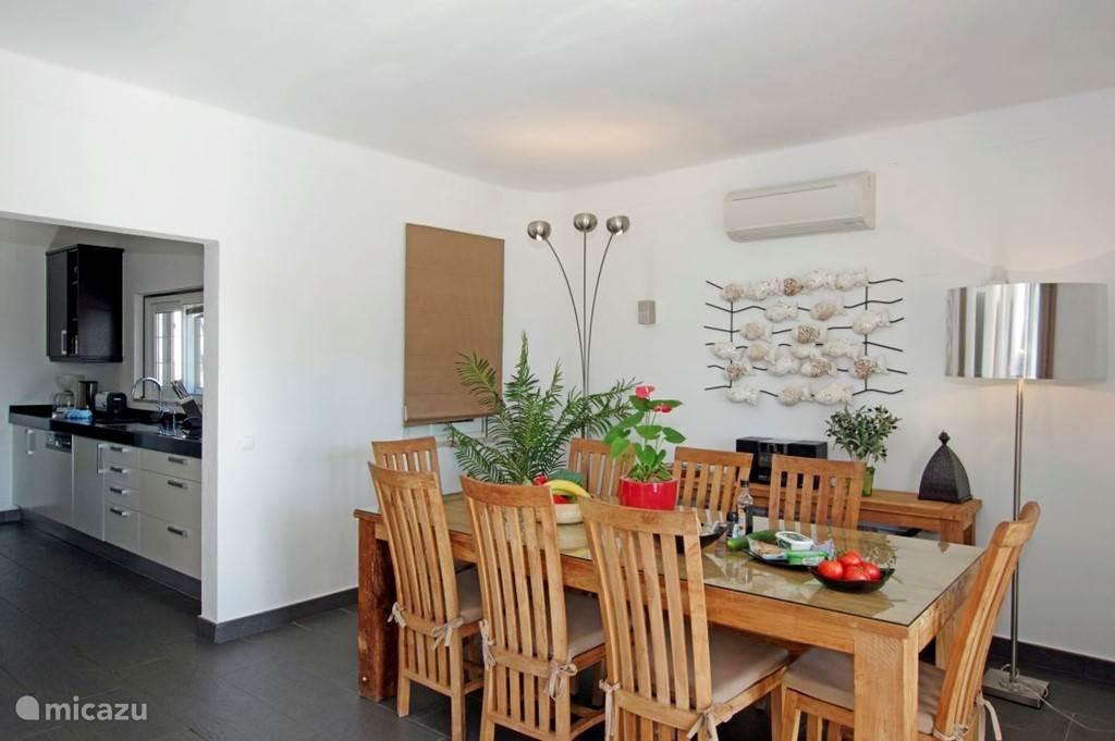 Eetkamer met teakhouten eettafel en stoelen en een schuifpui naar het (deels overdekte) terras