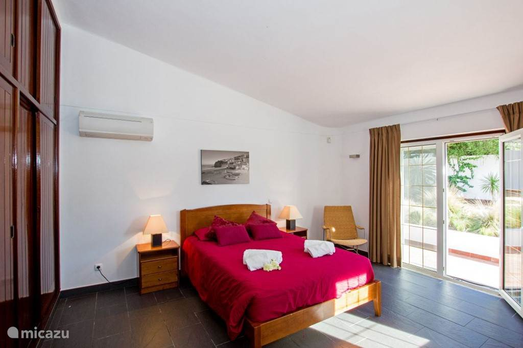 Foto 2 van slaapkamer 1. Deze slaapkamer heeft een openslaande tuindeuren en een tweepersoons bed van 140 x 200 cm.