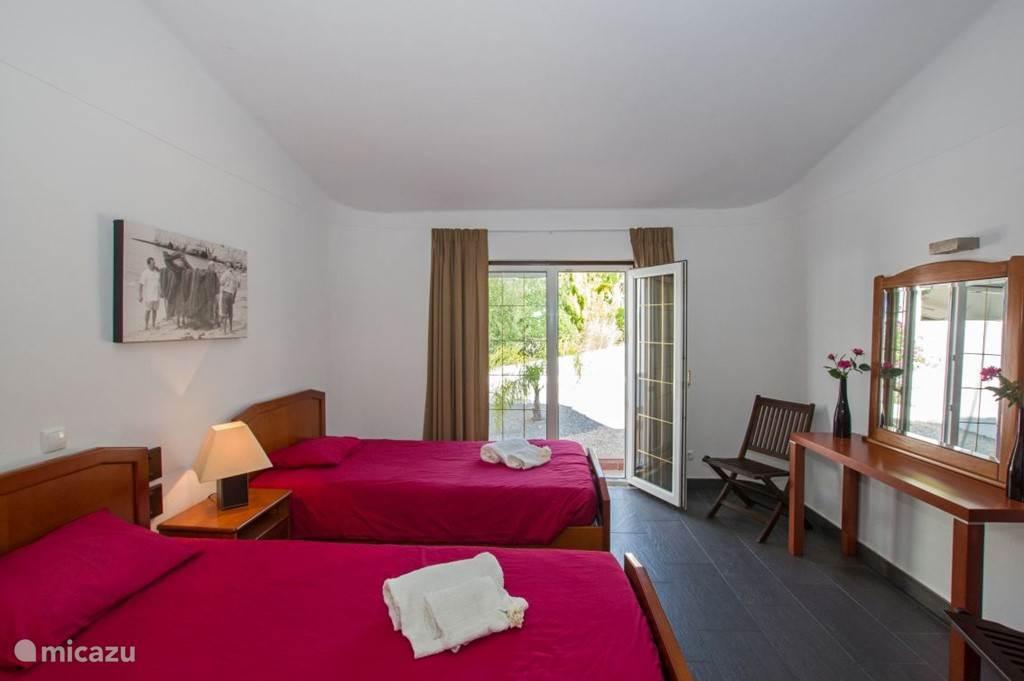 Slaapkamer 2 met openslaande tuindeuren en 2 eenpersoons bedden.