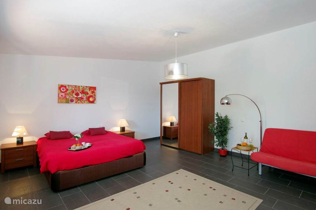 Slaapgedeelte guesthouse met kingsize bed en kledingkast en zit/slaapbank (140 x 190 cm.)