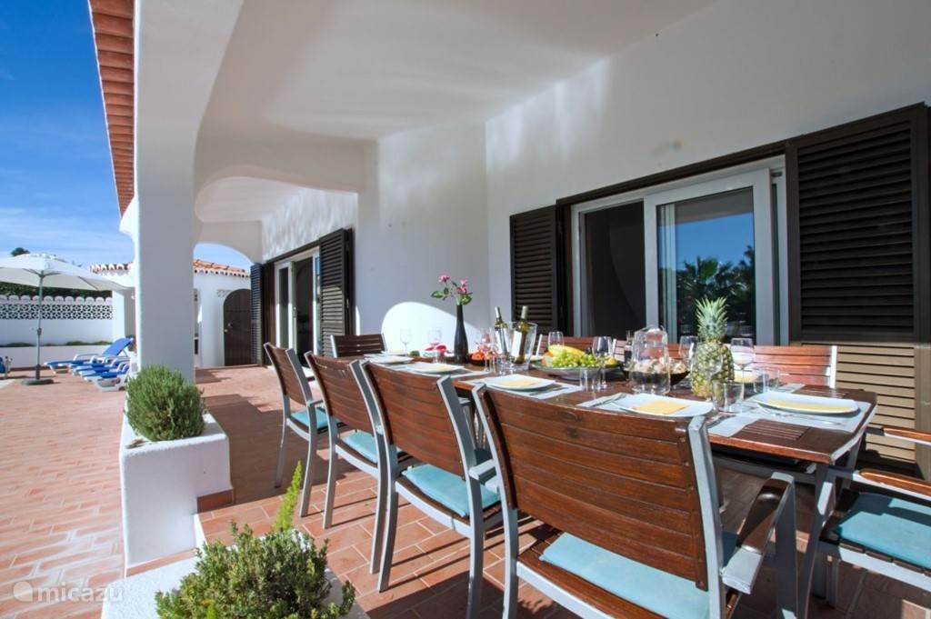 Overdekt terras met 10-persoons eettafel, welke eventueel in te schuiven is voor 6-8 personen.