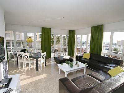 Dit is de woonkamer met het terras erom heen met het zicht op de haven en het strand.
