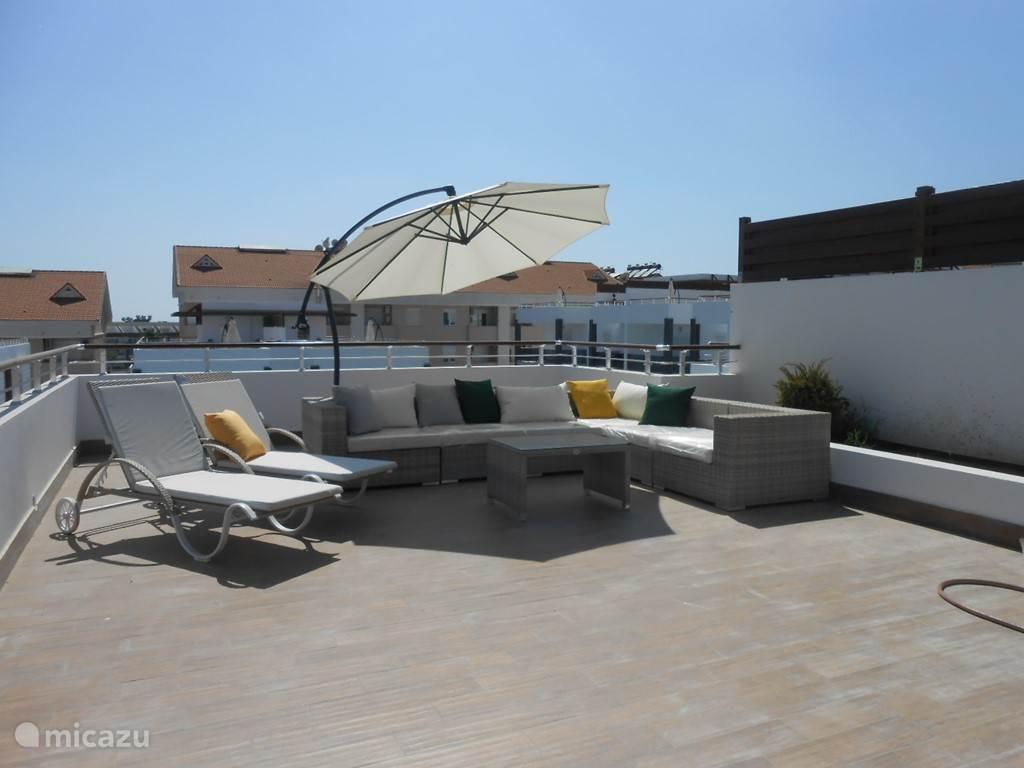 Het ruime dak terras met loungeset en ligstoelen