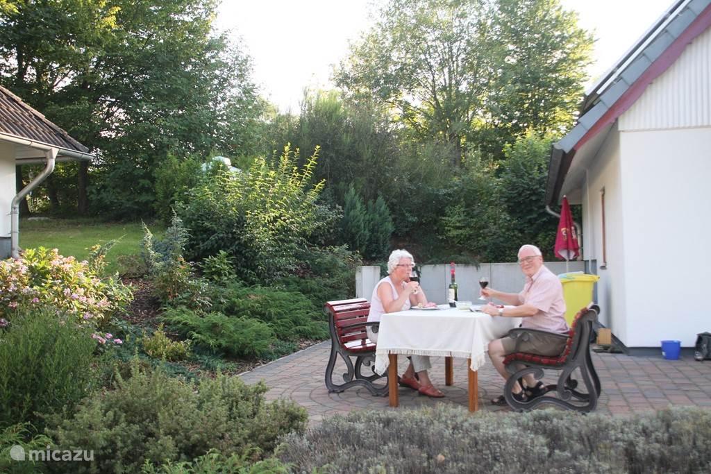 Ruim terras omringd door flinke gevarieerde tuin.