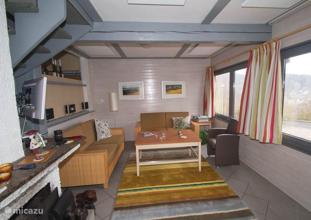 Woonkamer met twee 2,5 zits banken en leren fauteuil en mooi wollen vloerkleed. Tevens enkele infrarood panelen zichtbaar.