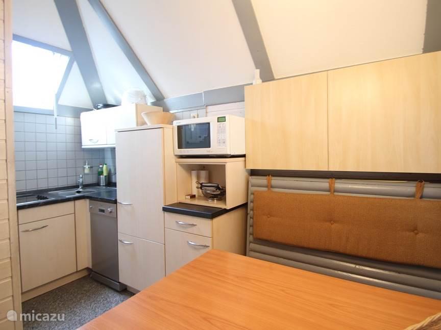 Keuken met 4-pits elektrisch fornuis, vaatwasser, koelkast, combi-magnetron en opbergkastjes.
