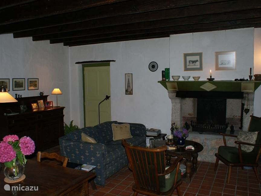 The kitchen with sitting by the fireplace and oak farm dining table. The door on the left is the entrance to the bathroom on the ground floor.