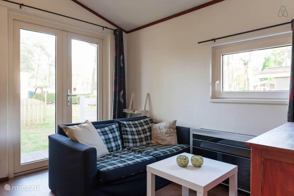 De huiskamer met zitbank, eethoek en TV
