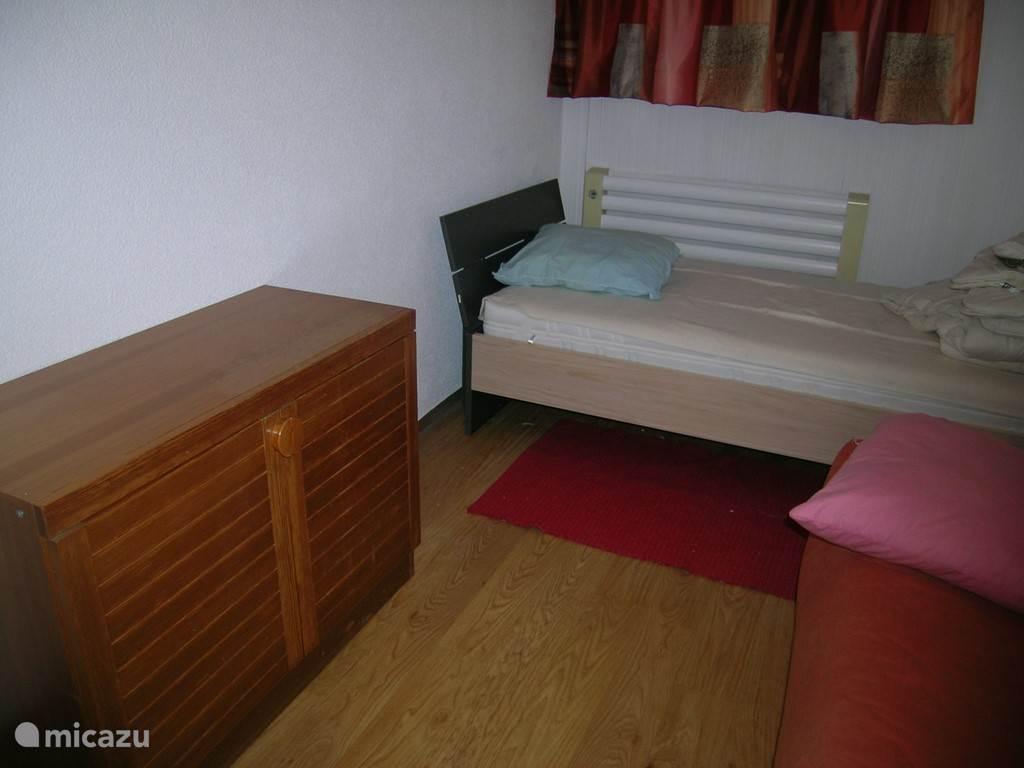 slaapkamer bestaat uit 1 persoonsbed,1 uitklapbare sofa(rechts) 90x120 cm , 2 kledingskasten en en laag kastje  Met 2 dubbele ramen uitzicht voorkant huis