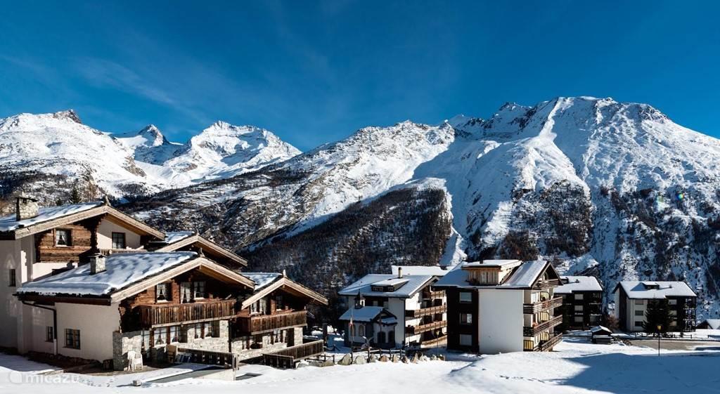 Winter uitzicht vanuit de zijkant van het terras op de dichtsbijzijnde gebouwen en bergen.