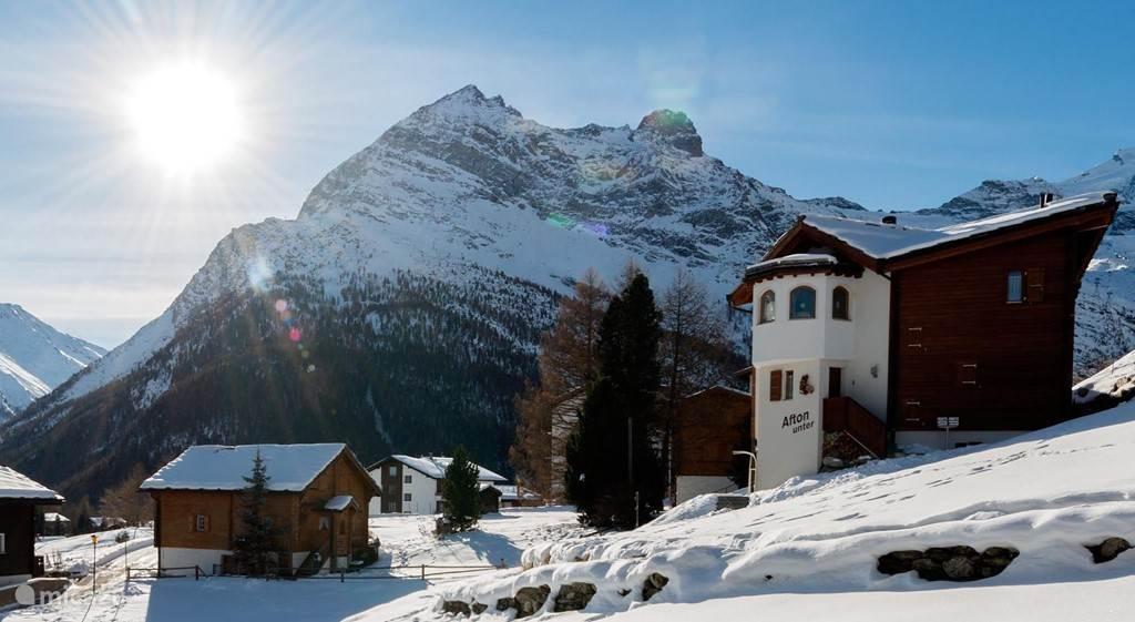 Winter uitzicht  vanuit de voorkant  van het terras op de omgeving , de buren en de bergen (ski gebied)
