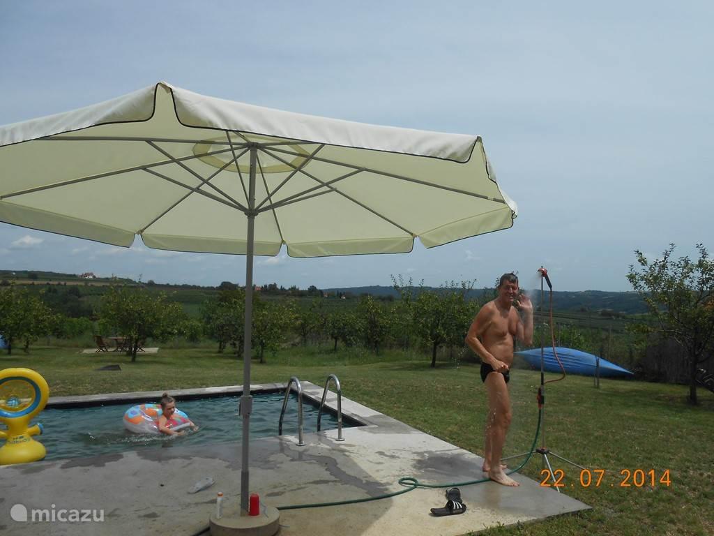 ...met de bal in het water gespeeld...en dan een douche nemen alvorens te gaan zonnebaden... Het water is in de zomer gemakkelijk 25 à 28°C. Op de achtergrond ligt ook nog een blauwe kajak waarmee op een rivier gevaren kan worden...