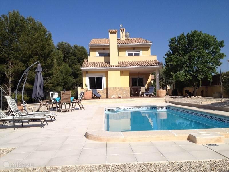 Zicht op het huis vanuit de achtertuin. Het zwembad heeft een gunstige zonligging.