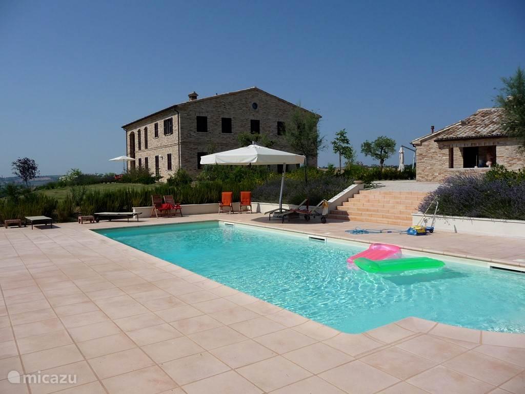 De villa en het bijgebouw gezien vanuit het zwembad. Door de situering in een helling ligt het zwembad erg beschut.