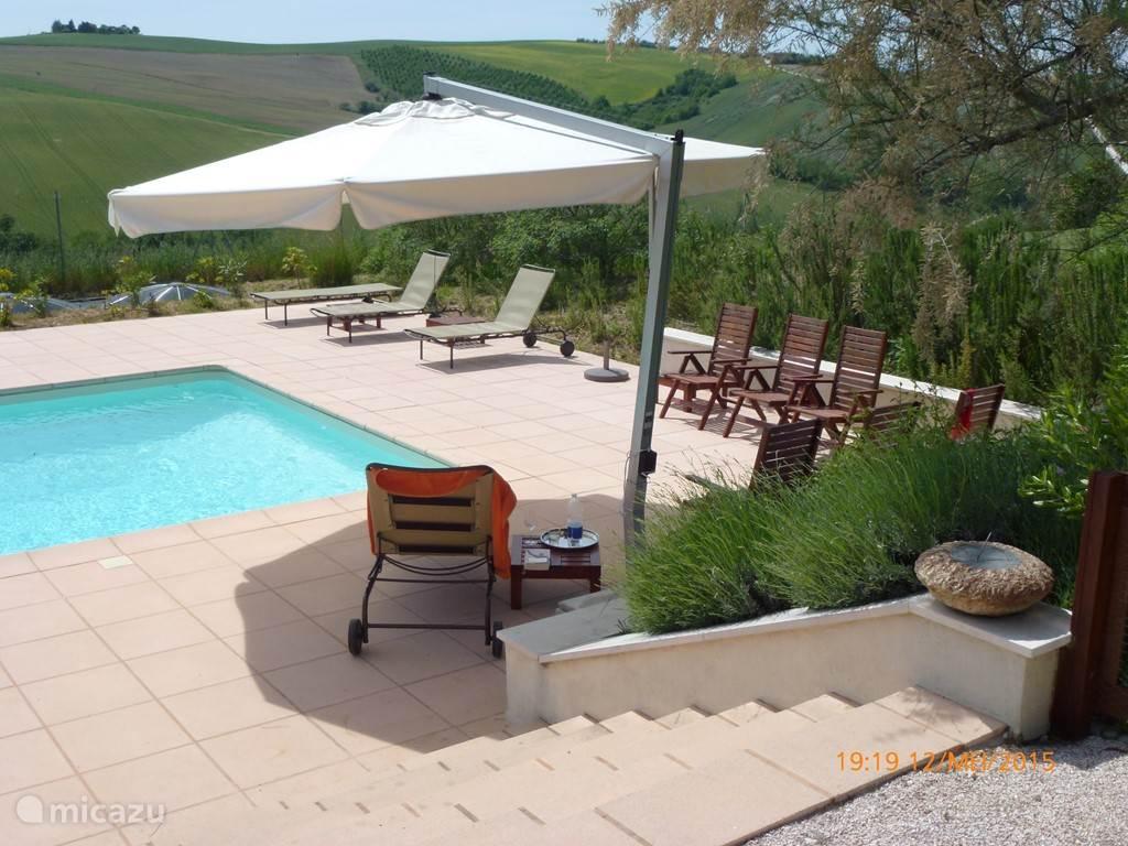 Zicht op het zwembad en de terrassen rond het bad