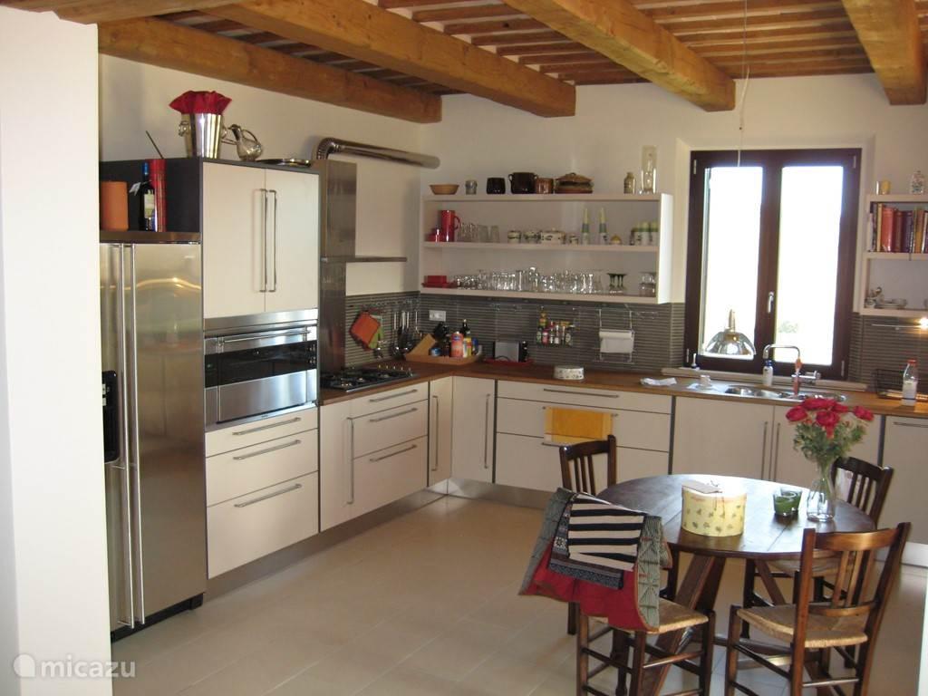Een impressie van de uitgebreide keuken met grote oven, ruime ijskast en vriezer met ijsmachine, afwasmachine, magnetron, etc. Het klassieke plafond, bestaande uit balken en tegels is goed zichtbaar.