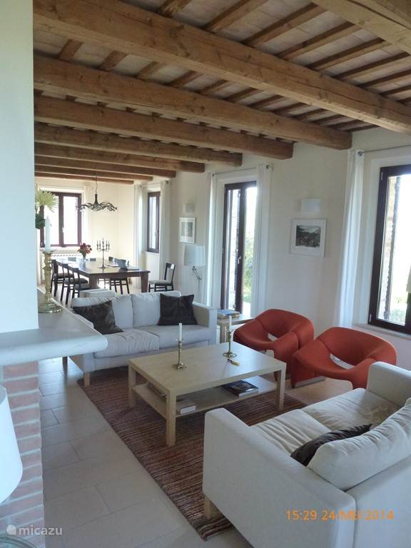 De woonkamer met de open haard, en achterin de grote klassieke Italiaanse eettafel