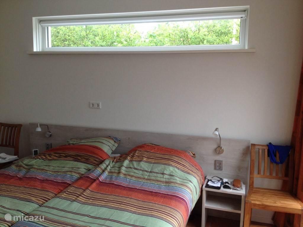 U kunt vanuit deze slaapkamer via de schuifdeuren het terras op!