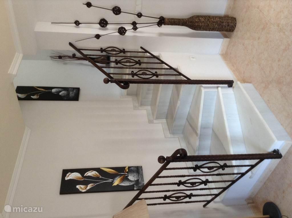 In de woonkamer is de vaste trap naar bovenverdieping