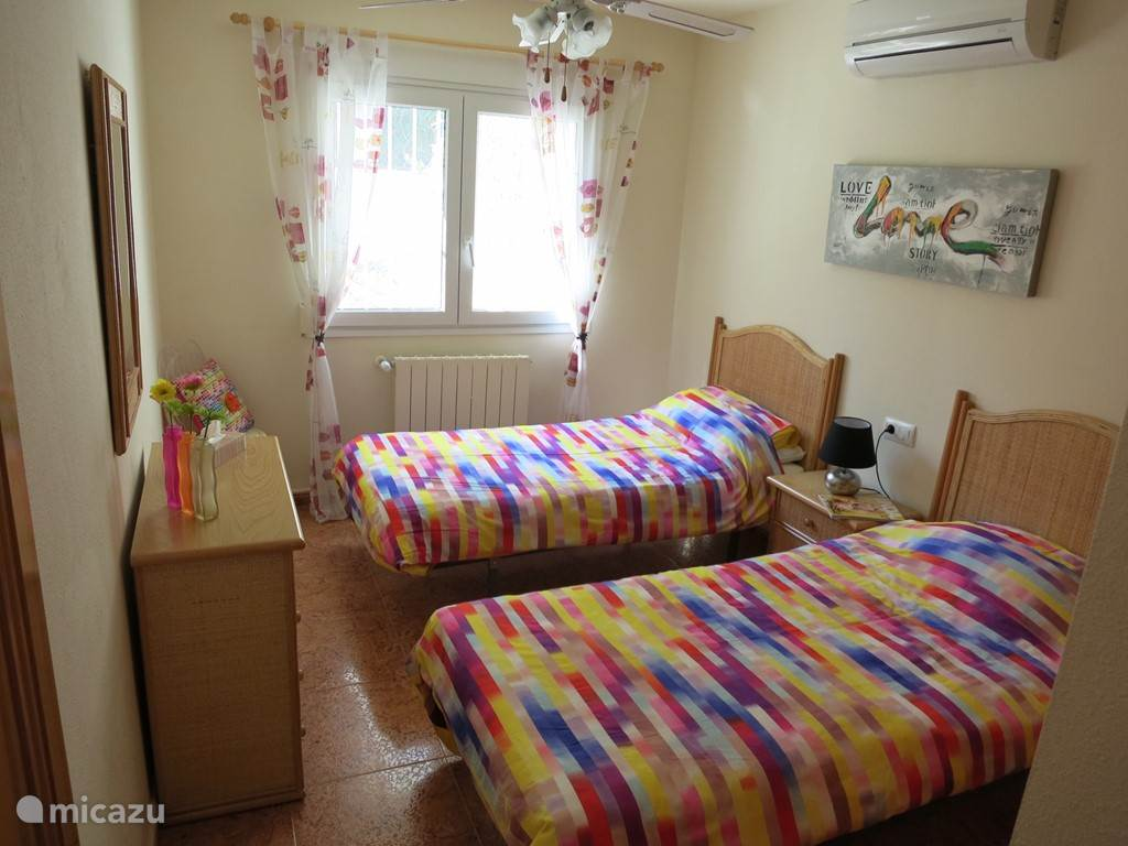 Slaapkamer op de eerste etage met twee aparte bedden en grote inbouwkast