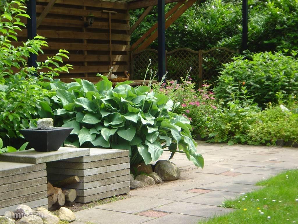 In de tuin bevindt zich een terrasoverkapping met tuinmeubilair.