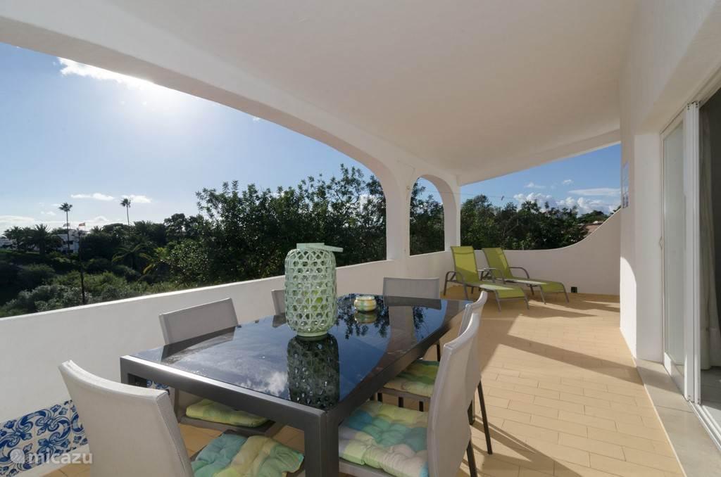 Het overdekte terras kijkt uit over te tuinen en heeft zelf zeezicht