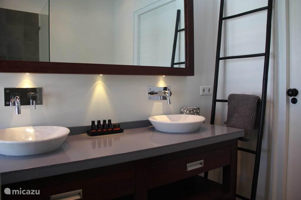 Luxe badkamer met grote spiegel en dubbele wastafel.
