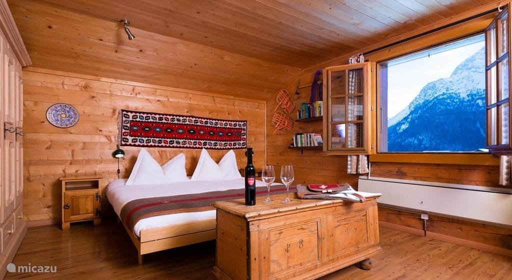 slaapkamer met  een 2 persoonsbed , kledingkast, 2 antieke kisten, bureau, stoelen, spiegel en wastafel
