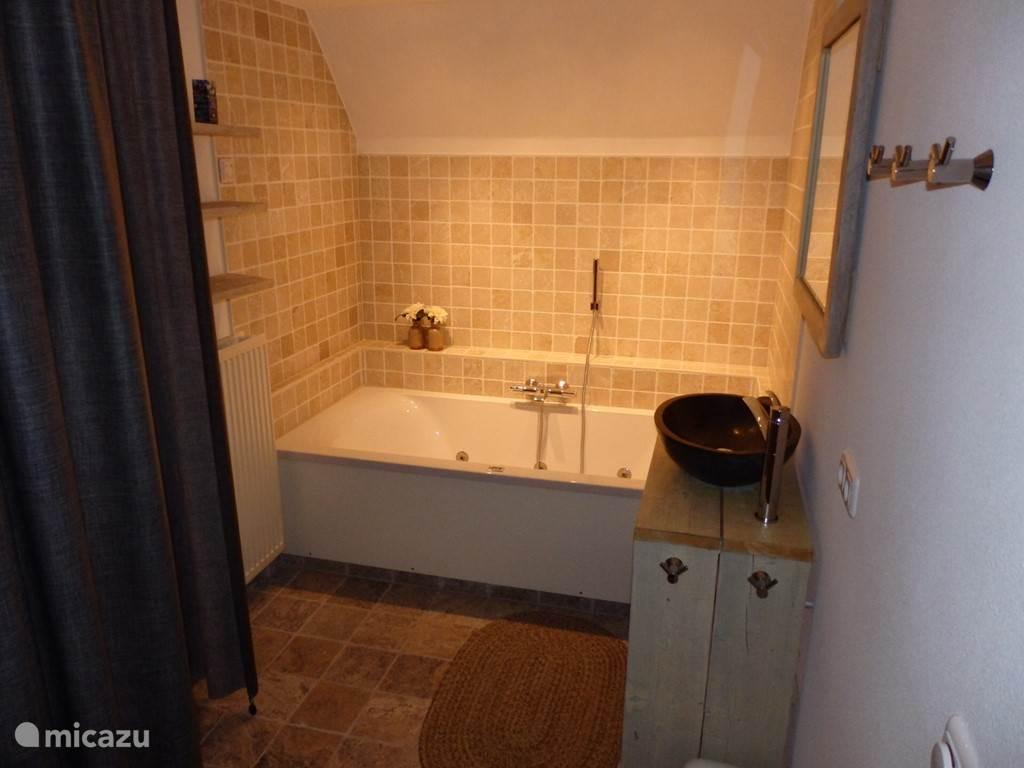 Badkamer bubbelbad en licht therapie en dimbare spotjes voor de juiste sfeer.