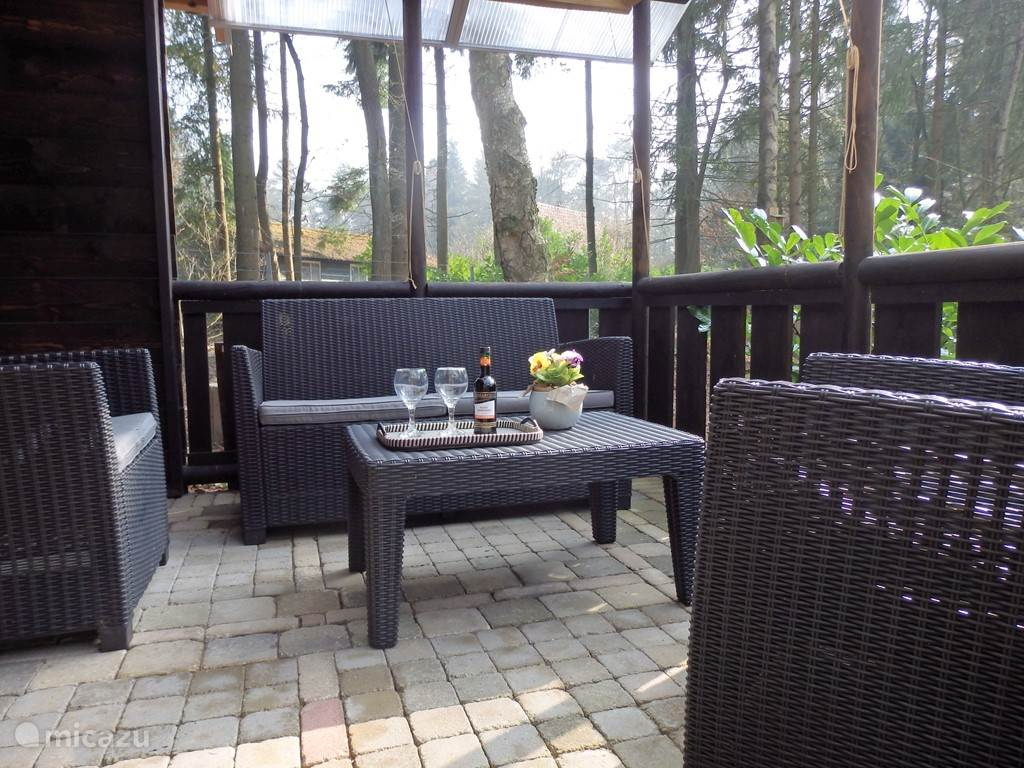 Overdekt terras met lounge set. Voor de privacy i.v.m. sauna gebruik kunt u de ruimte afsluiten d.m.v. bamboe rolgordijnen.